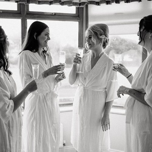 black and white image of the bridesmaids toasting to champagne