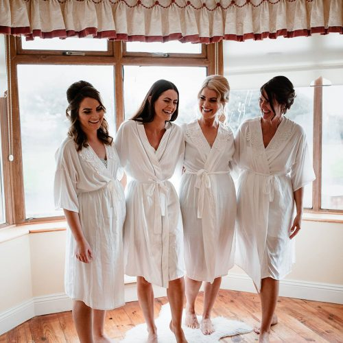 image of the bridesmaids in their white robes laughing