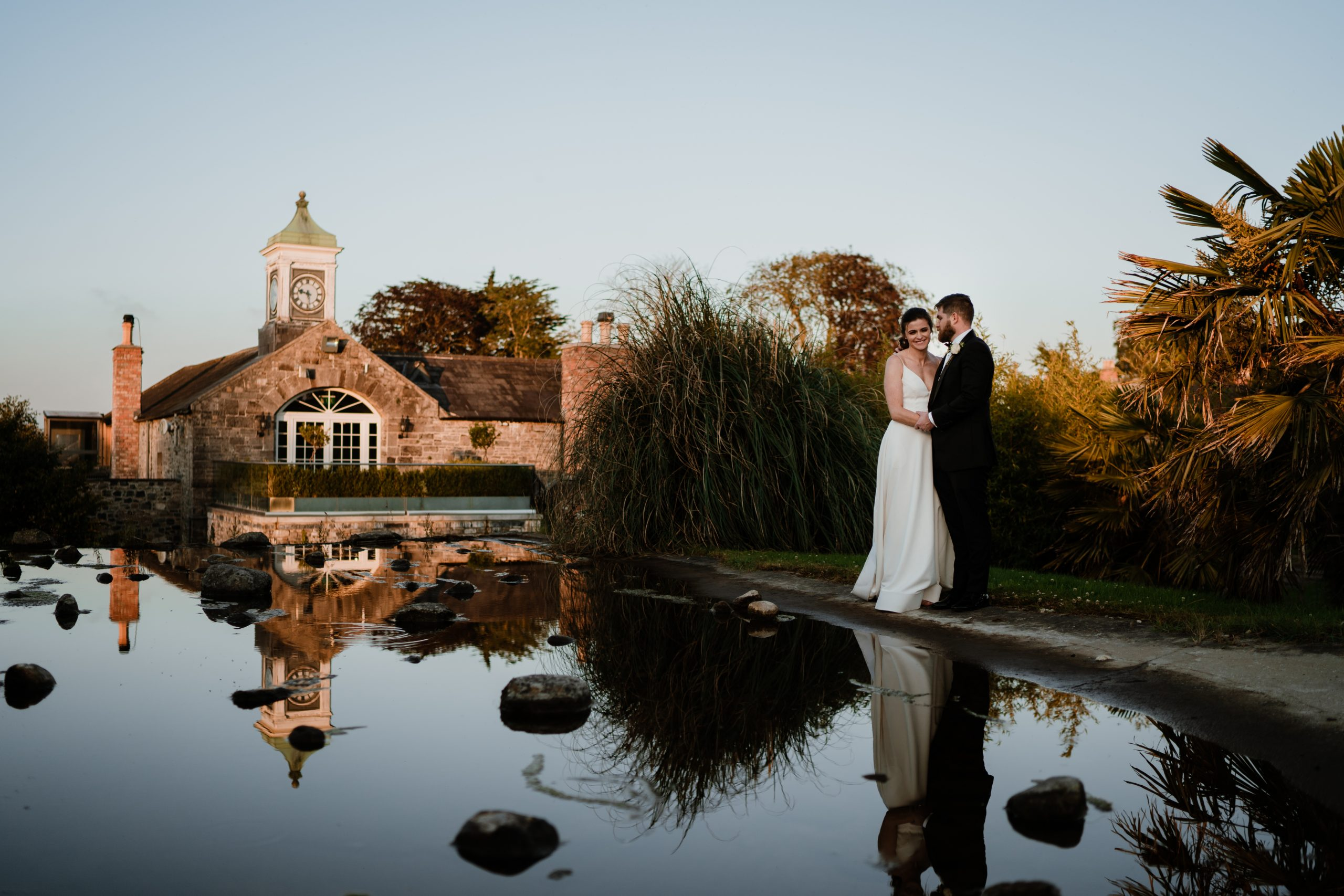 bride and groom standing in front of a puddle in ballymagarvey village